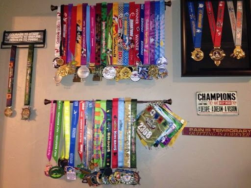 Simple, inexpensive way to hang medals. Use a curtain rod (under $6 at Walmart) and space how you like. Use hooks to hang bibs. Much less expensive than medal holders purchased online. running rac?