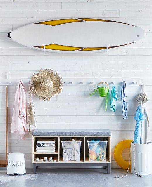 Keep beach gear stored with a rack for a surfboard, a seat to change with boxes filled with towels and beach gear underneath.