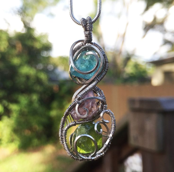 Spiralizer's Desire... Available at www.EarthStarCreation.com  #BlueBeryl #RedRuby #peridot #silver #wirewrap