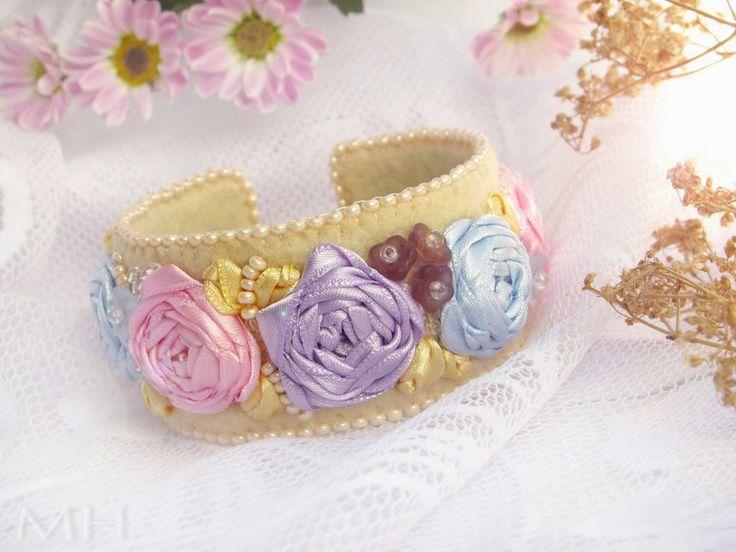 Líbezná Ambrienne  ... vždy zasněná, urozená svým původem i krásou.  Luxusní autorský náramek vhodný pro slavnostní příležitost, vytvořený kombinací stužkové a korálkové výšivky na plsti (silk ribbon embroidery a bead embroidery)  Na žlutém filcu je saténovými stužkami vyšito pět růžiček a lístečky. Doplňují je české skleněné mačkané kytičky, ...