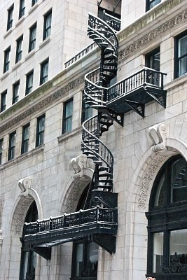ornate wrought iron spiral fire escape on the front of a highly decorated building in the snow