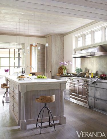 A cluster of delicate pendant lights floats above this kitchen island.: