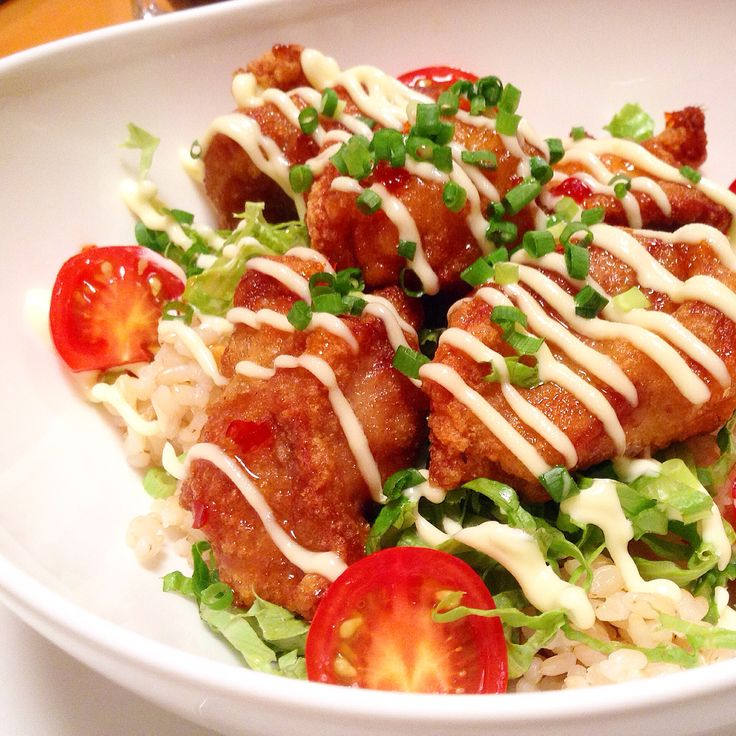 Japanese-style fried chicken on a bed of hot brown rice, garnished with tomatoes, spring onions and wasabi mayonnaise. www.travelifemagazine.com