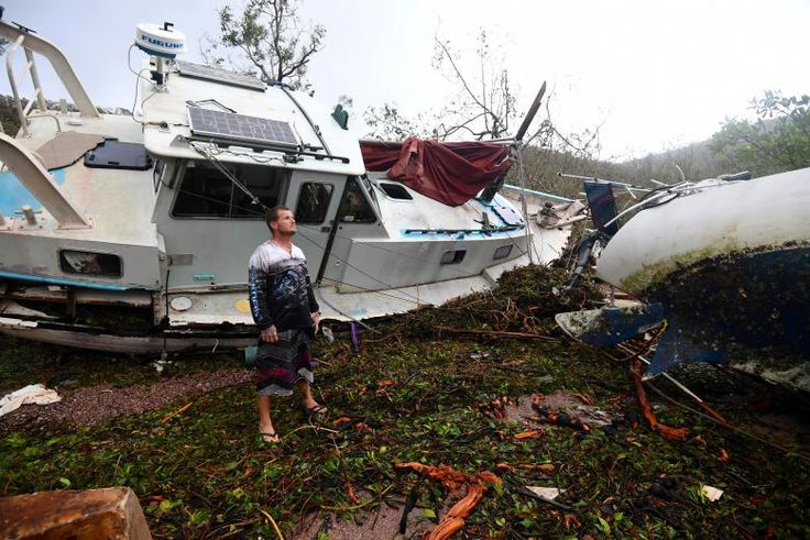 Local resident Bradley Mitchell inspects the damage to a relative's boat after it smashed against the bank after Cyclone Debbie passed through the township of Airlie Beach. AAP/Dan Peled/via REUTERS