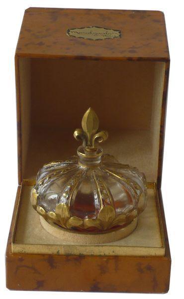 Marcel Guerlain « Le Roy le veult »  Flacon en verre partiellement doré figurant une couronne royale   surmontée d'un bouchon en forme de fleur de lys.