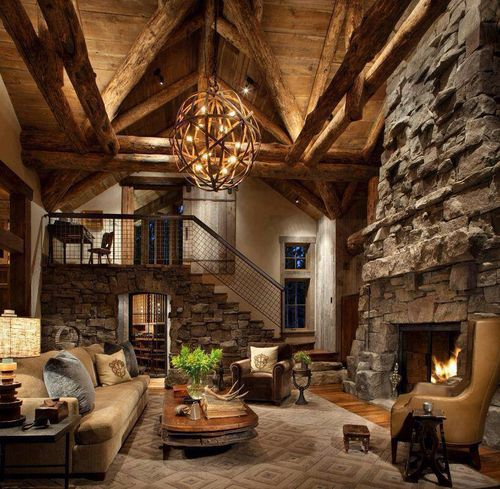 Luxury cabin living area. High ceilings, stone fireplace, and rustic chandelier.