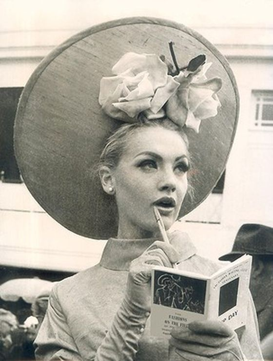 Margaret Wood of Essendon, looks thoughtful while reading in her skimmer, highlighted by roses. Melbourne Cup, Flemington. 1964.  Substantial prizes are awarded for the best dressed men and women, and the requirement of a hat or fascinator are part of the fun. In 1965, model Jean Shrimpton captured the world's attention by wearing a miniskirt to a raceday and competition for similar attention continues to be fierce.