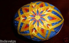 Temari Egg created with Yellow and Orange Thread over Bright Blue