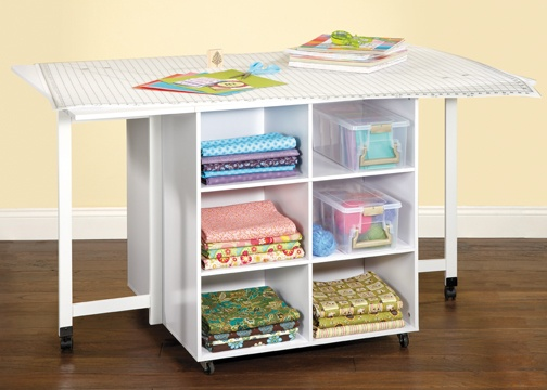 An {awesome} storage table with cubbies on both sides! The sides also fold down for storage! #organization