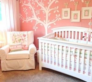 Quarto de bebê rosa com papel de parede árvore