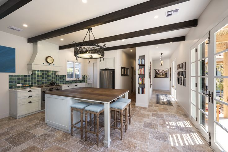 Mediterranean kitchen, handmade tile splashback, exposed beams, timber island bench, handpainted cabinets, wrought iron pendant light