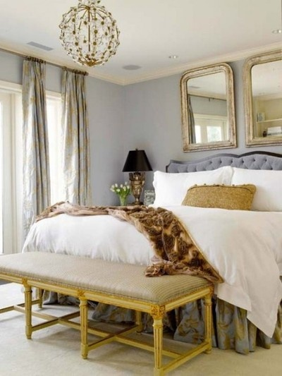 Gold and gray bedroom luxurious fabrics double mirrors over bed