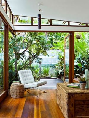 Modern living room in rainforest, large garden with glass walls, warm timber floors and white Barcelona chair