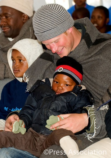 Prince Harry holds a child on his knee as he and Prince William visit Semongkong Children's Centre in Lesotho