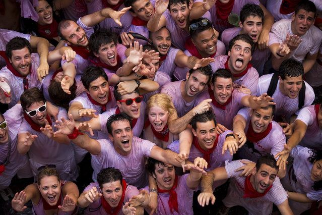 """Revelers react while they ask for water to be thrown from balconies during the launch of the """"Chupinazo"""" rocket, to celebrate the official opening of the 2013 San Fermin fiestas, Saturday, July 6, 2013 in Pamplona, Spain. (Photo by Daniel Ochoa de Olza/AP Photo)"""