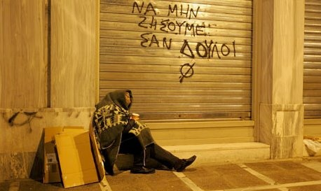 Hambre y pobreza en Atenas (1). The graffiti reads: 'We shoud not live as slaves.'
