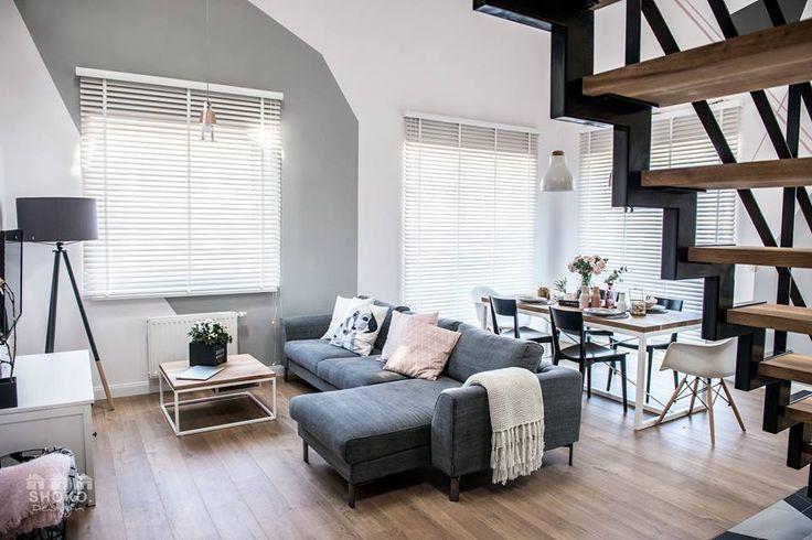 Aranżacja wysokiego salonu z szarą sofą