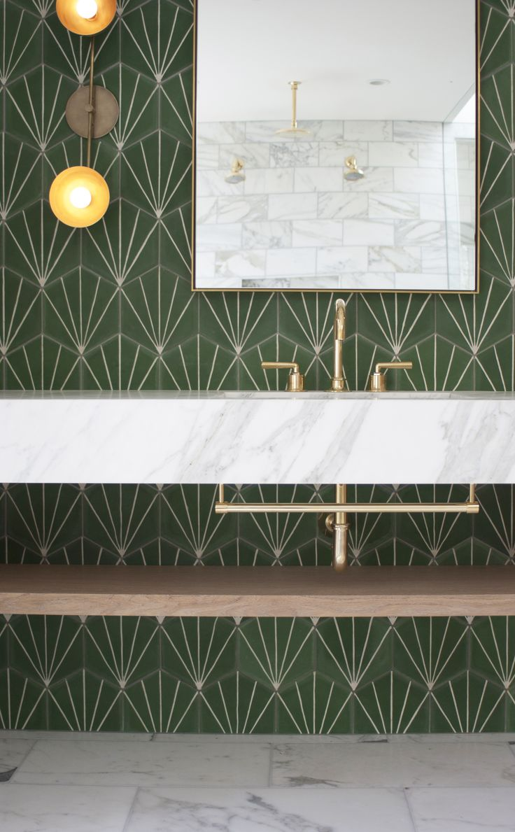 Green cement tile and marble counter with brass hardware and sconces in a modern master bath