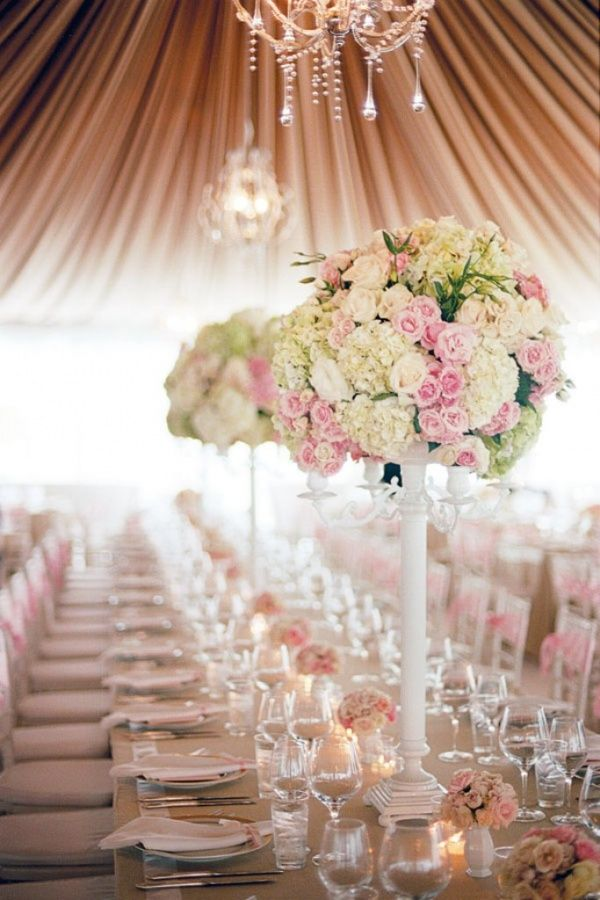 Tall centerpiece of white hydrangea, pink roses & lisianthus on a white candelabra
