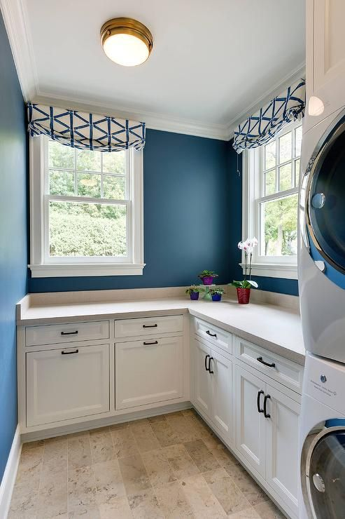 A blue and white laundry room is viewed with bold blue painted walls and white cabinetry.