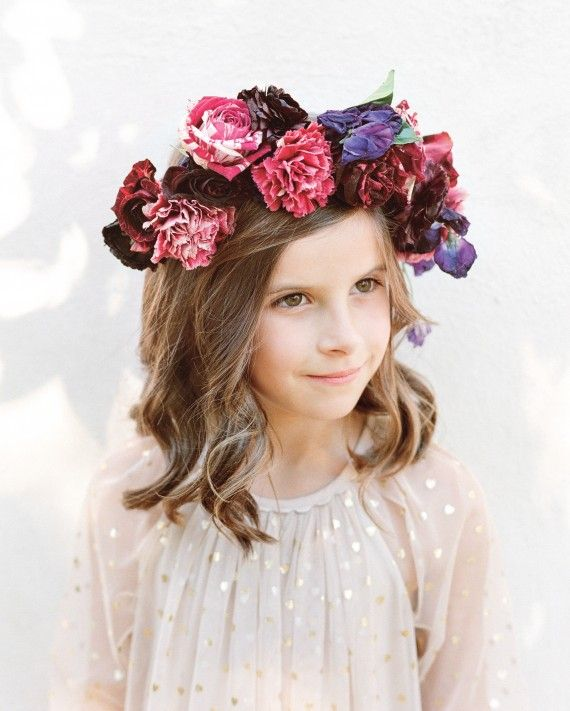 This flower girl's pretty pink and purple floral crown was woven of speckled garden roses, ranunculus, and sweet peas.