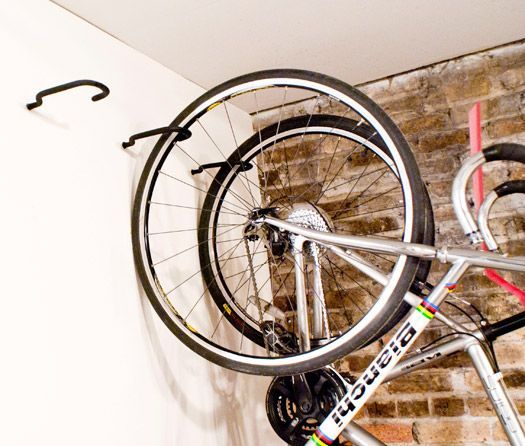 Move ceiling hooks to wall... bike supported  by only one hook -- and it means room for many bikes