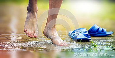 Barefoot the feet of the boy and ankle in a mud puddle
