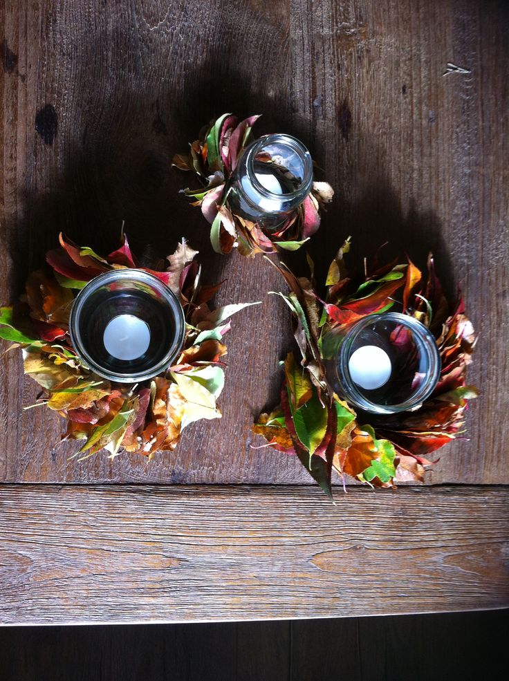 Herfstkransjes van blaadjes uit het bos en in het midden potjes met waxinelichtjes er in.