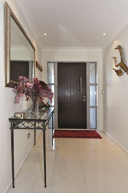A dark timber door and crisp white tiles form a striking entranceway.