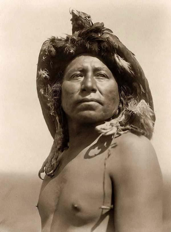 You are looking at an intriguing picture of a Crow Medicine Man. It was taken in 1908 by Edward S. Curtis.    The picture presentsa Crow (Apsaroke) Shaman, barechested and wearing an eagle head dress. This man has a proud look on his face, and is pictured standing outdoors