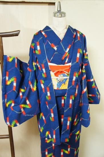 深みのあるブルー地に、オレンジや黄色、緑などの外国の絵本を思わせるポップキュートなカラーリングでアルファベットのNのようなモダン幾何学模様が織り出されたウールのアンサンブル(羽織と着物のセット)です。