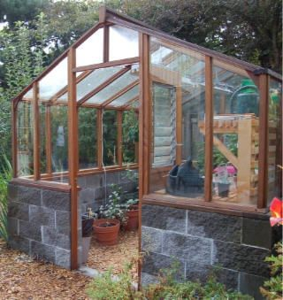 Greenhouse with brick base. I would think the stone would absorb heat in the day and release it overnight making temps more stable