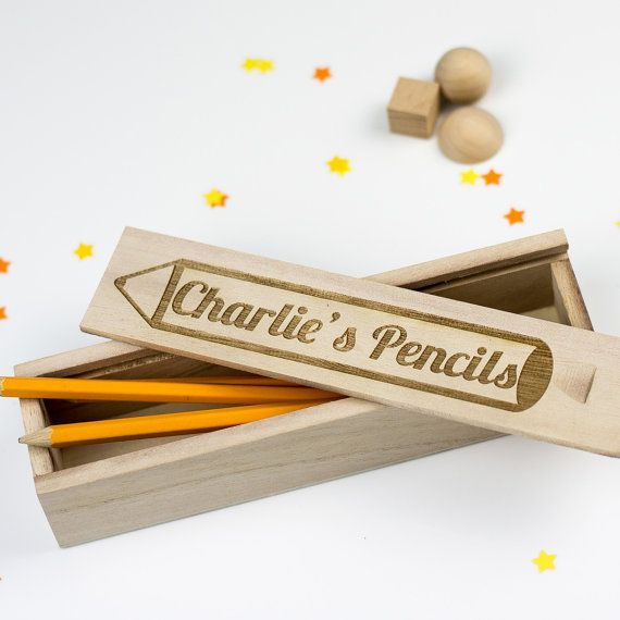 This personalised wooden pencil box features an engraved drawing of a pencil…