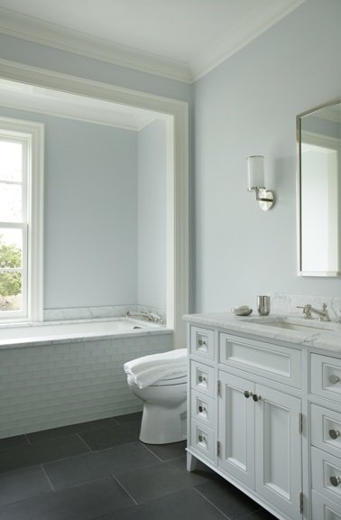 Love everything about this - especially the tub surround and framing! White and pale blue/gray bathroom with gray floor and subway tile