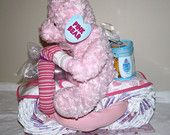 teddy bear on a motorbike made from nappy cakes. with blankets, bibs and bath products   made by Babys Precious Gifts