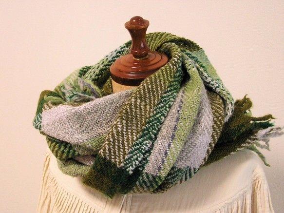 グリーンのグラデーションでチェック柄に織りました。手紡ぎの羊毛糸は空気を含むのでとても暖かいのが特徴です。たっぷりとした長さなので垂らしたり、ぐるぐる巻きにしてみたり。細目の糸で織っているので巻いてみると意外と軽く感じると思います。(230g)・サイズ43cm×170cm(フリンジの長さ含む)・素材 メリノ・お手入れ方法 おしゃれ着用洗剤を使用し、ぬるま湯で手洗いした後、 タオルで巻いて水分を取り平置きして乾かしてください。  形を整えスチームアイロンを当てると完璧です。