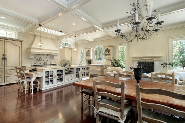 Great room living area with large white kitchen, dark wood wood floors and elevated white-beamed ceiling