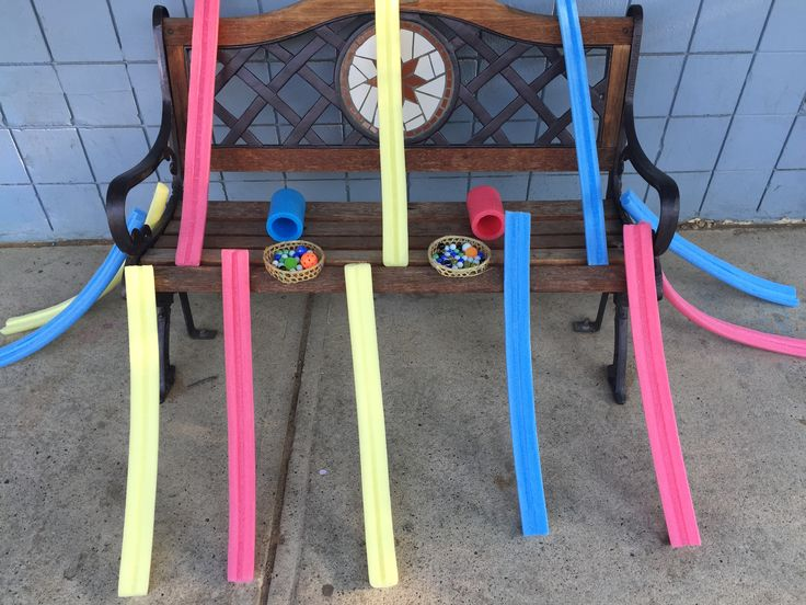 An Invitation to Play: Exploring gravity, speed, velocity, weight, etc. We set up a provocation at our Outdoor Play workshop using pool noodles cut open lengthwise and marbles.