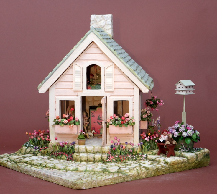 "The Pink Playhouse, by Polly Morris, 1996, front view. Look inside to see some of the toys. I made the pretty fireplace screen with the swooping swifts, inspired by a 1916 illustration for ""Polly Put the Kettle On"", by Dorothy Wheeler. Here is a link: http://www.klingarts.com/pp/wheeler/"