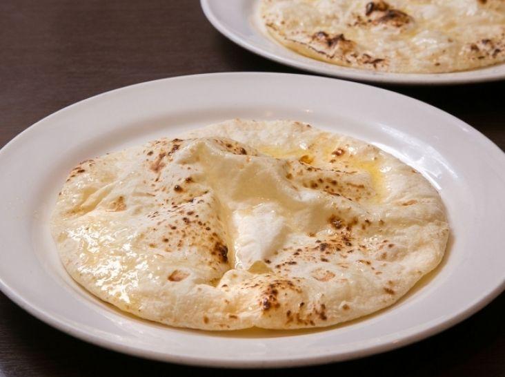 ナン(フライパンで焼く家庭バージョン) - 藤井 正樹シェフのレシピ。ナンは、ベーキングパウダーとダヒ(ヨーグルト)で発酵させ、タンドールという土釜で焼いたパンを言い、インドでは本来レストランで食べるものです。 今回は家庭で楽しめる、フライパンで焼くバージョンをご紹介します! ポイントは、生地をなめらかに練ること。発酵の仕方で風味が変わります。