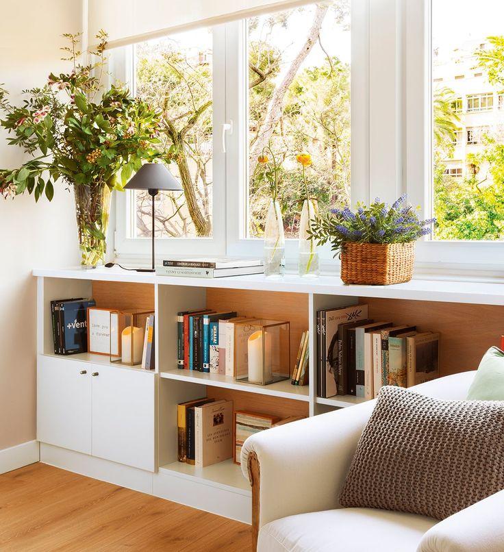 Librería blanca bajo la ventana con flores y plantas encima