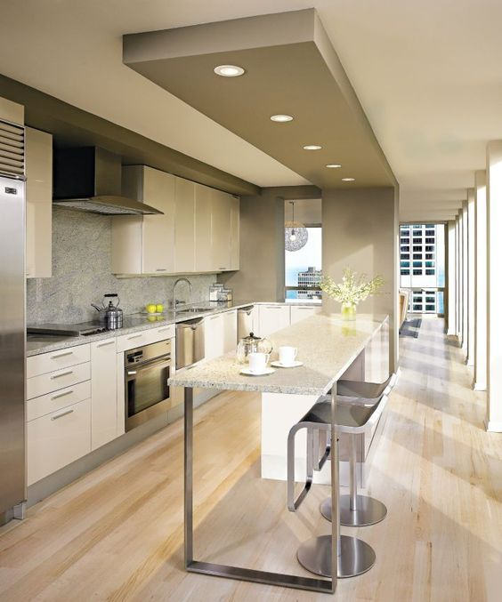 This contemporary kitchen is at the center of this U-shaped apartment, forming a natural path between the two wings of the residence.