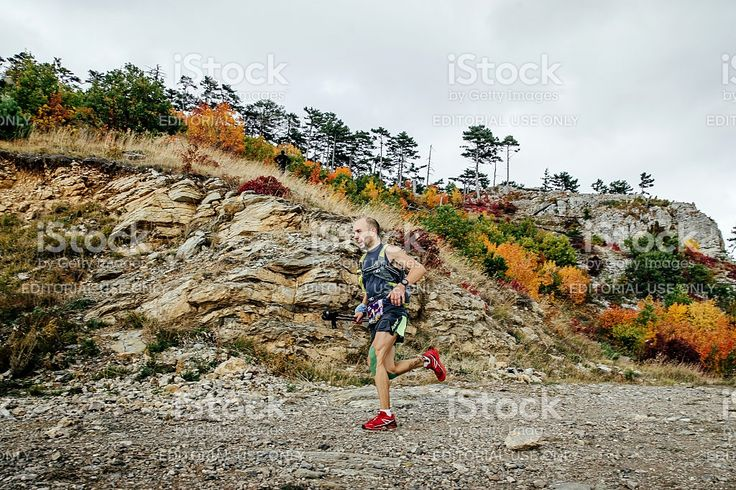 Yalta, Russia - October 5, 2016: athlete runner running with walking sticks on a mountain trail in autumn landscape during Crimea mountain marathon
