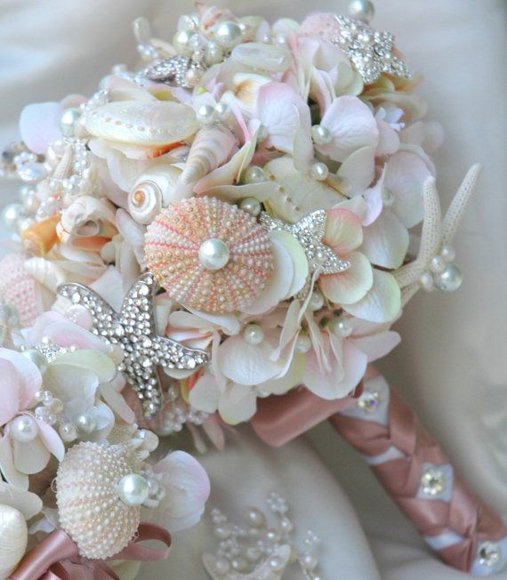 This lovely Sea shell wedding bouquet uses blush pink shells.A dozen starfish crystal rhinestone brooches takes this bouquet to the sublime.