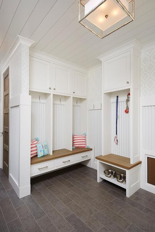 Cottage mudroom features a shiplap ceiling over mudroom lockers over a built in bench fitted with drawers atop taupe tiled floors.