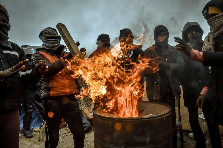 """Calais, France - 1er mars 2016 - Avec 8 Celsius, les migrants se réchauffent autour d'un feu alimenter avec le bois que les hommes de chantier ont mis par terre lors du démantèlement de la """"Jungle """" de Calais."""