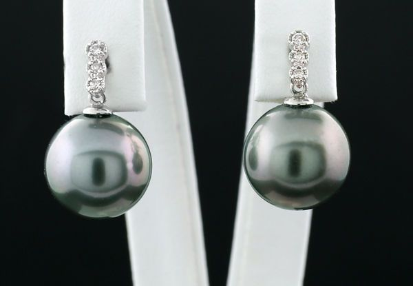 Een paar oorbellen met Tahitiaanse parels en diamanten licht antracietgrijze Tahitiaanse parels van 117 mm in doorsnede 750 witgoud -- Geen minimumprijs  2 fine bright anthracite grey Tahitian cultivated pearls of approx. 11.7 mm in diameter silvery overtone very fine lustre normal Tahitian pearl typical growth characteristics. Connected flexibly on mounts carrying 6 diamonds with a total of 0.08 ct I/SI-P. Set on studs made of and hallmarked as 750 / 18 kt white gold on the studs. The studs…