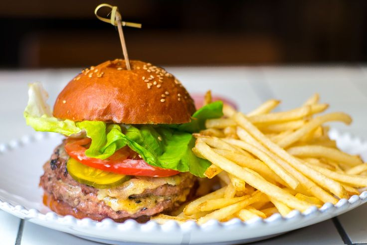 George Mendes's Flatiron Portuguese restaurant Lupulo serves a burger featuring a flame-grilled double patty stack that evokes Burger King's Whopper. The meat is cooked on a massive charcoal-powered Grillworks grill.