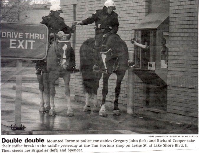 Double double... Mounted Toronto police constables Gregory John (left) and Richard Cooper take their coffee break in the saddle yesterday at the Tim Horton's shop on Leslie St. at Lake Shore Blvd. E. Their steeds are Brigadier (left) and Spencer.