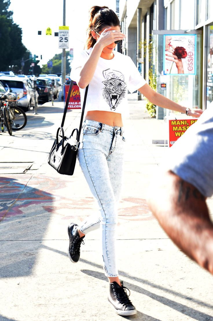 Kendall Jenner (Loose White Graphic Crop Top, Light Acid Wash Jeans, Black Hightops, Ponytail)